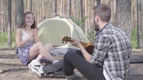 Ο νεαρός άνδρας που παίζει ukulele στη σκηνή ενώ αρκετά νέα συνεδρίαση γυναικών μπροστά από τον που χτυπά τα χέρια Αγαπώντας ζεύγ απόθεμα βίντεο