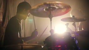 Ο νεαρός άνδρας που παίζουν συναισθηματικά τα τύμπανα σε μια ορχήστρα ροκ και οι κιθάρες παίζουν στο υπόβαθρο απόθεμα βίντεο