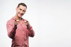Ο νεαρός άνδρας που φορά το ελεγμένο κόκκινο πουκάμισο παρουσιάζει ότι το σημάδι δείχνει το πτερύγιό του Στοκ Εικόνα