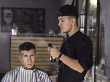 Ο νεαρός άνδρας προετοιμάζεται να πάρει το κούρεμα από τον κουρέα καθμένος στην καρέκλα στο barbershop Στοκ Εικόνες