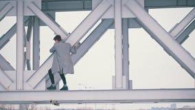 Ο νεαρός άνδρας σε ένα γκρίζο παλτό αναρριχείται στην έκταση γεφυρών απόθεμα βίντεο