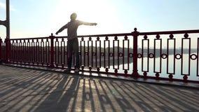 Ο νεαρός άνδρας στέκεται κοντά στα κιγκλιδώματα μιας γέφυρας πέρα από το Dnipro στο ηλιοβασίλεμα στην slo-Mo απόθεμα βίντεο