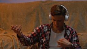 Ο νεαρός άνδρας στα ακουστικά που ακούει τη μουσική, αόρατη κιθάρα παιχνιδιού, χαλαρώνει απόθεμα βίντεο