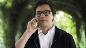 Ο νεαρός άνδρας στα γυαλιά μιλά στο τηλέφωνό του και περπατά σε ένα πάρκο φιλμ μικρού μήκους