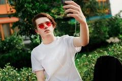 Ο νεαρός άνδρας στα κόκκινα γυαλιά παίρνει selfie στο πάρκο στοκ φωτογραφία
