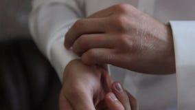 Ο νεαρός άνδρας στερεώνει το μανίκι του πουκάμισού του φιλμ μικρού μήκους