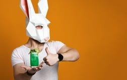 Ο νεαρός άνδρας στη μάσκα κουνελιών εγγράφου και η λευκιά μπλούζα που πίνει το πράσινο κοκτέιλ πίνουν στοκ εικόνες
