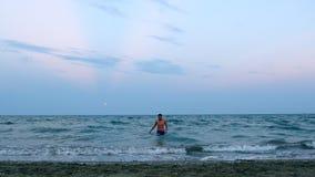 Ο νεαρός άνδρας στον μπλε οσμηρό βγαίνει από το μπλε θαλάσσιο νερό μέσα στην παραλία καμερών φιλμ μικρού μήκους