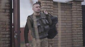 Ο νεαρός άνδρας στους στρατιωτικούς περίβολους με τη μεγάλη τσάντα που εισάγει την πύλη Ένα άτομο επιστρέφει από το σπίτι στρατιω απόθεμα βίντεο