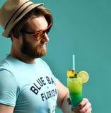 Ο νεαρός άνδρας στο καπέλο που πίνει το κοκτέιλ της Μαργαρίτα πίνει την ευτυχή εξέταση χυμού τη κάμερα Στοκ Εικόνες