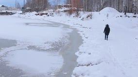 Ο νεαρός άνδρας στο μαύρο σακάκι με την κουκούλα γουνών είναι στις χιονισμένες όχθεις του παγωμένου ποταμού απόθεμα βίντεο