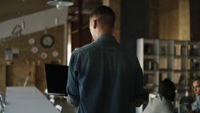 Ο νεαρός άνδρας στο πουκάμισο τζιν περπατά με ένα lap-top στο χέρι και τη δακτυλογράφησή του Καυκάσιο άτομο που απασχολείται δημό απόθεμα βίντεο
