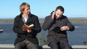 Ο νεαρός άνδρας στο τηλέφωνο ενοχλεί το άτομο withbook Στοκ Φωτογραφία