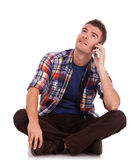 Ο νεαρός άνδρας στο τηλέφωνο που κάθεται ανατρέχει Στοκ φωτογραφία με δικαίωμα ελεύθερης χρήσης