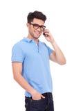 Ο νεαρός άνδρας στο τηλέφωνο χαμογελά Στοκ φωτογραφία με δικαίωμα ελεύθερης χρήσης