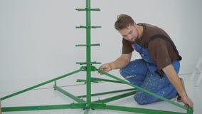 Ο νεαρός άνδρας συγκεντρώνει το δέντρο πλαισίων, καθμένος στο εσωτερικό φιλμ μικρού μήκους