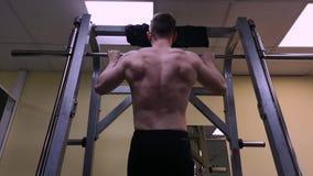 Ο νεαρός άνδρας συμμετέχει στην ικανότητα στη γυμναστική Ο αθλητής σηκώνεται στο φραγμό φιλμ μικρού μήκους
