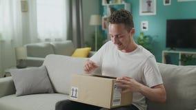 Ο νεαρός άνδρας τινάζει και ανοίγει το δέμα χαρτονιού με το ενδιαφέρον απόθεμα βίντεο