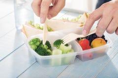 Ο νεαρός άνδρας τρώει το υγιές γεύμα από το καλαθάκι με φαγητό Στοκ Φωτογραφίες