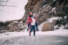 Ο νεαρός άνδρας φέρνει τη φίλη του στην πλάτη πέρα από τη λακκούβα του λειωμένου νερού Γέλια ζεύγους στοκ φωτογραφίες