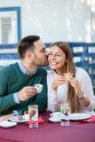 Ο νεαρός άνδρας φιλά τη φίλη του στο μάγουλο, που πίνει τον καφέ σε έναν καφέ στοκ εικόνα με δικαίωμα ελεύθερης χρήσης