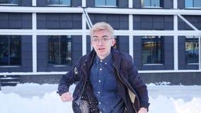 Ο νεαρός άνδρας χαίρεται και πηδά στο χιόνι φιλμ μικρού μήκους