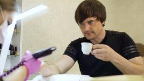 Ο νεαρός άνδρας χαλαρώνουν και ο καφές κατανάλωσης κατά τη διάρκεια της διαδικασίας του μανικιούρ απόθεμα βίντεο