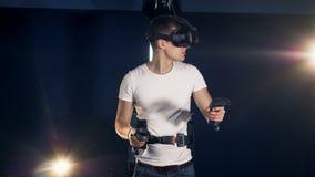 Ο νεαρός άνδρας χρησιμοποιεί μια συσκευή εικονικής πραγματικότητας και κινεί τα χέρια Παίζοντας παιχνίδι 360 κασκών εικονικής πρα απόθεμα βίντεο