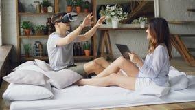 Ο νεαρός άνδρας χρησιμοποιεί τα γυαλιά εικονικής πραγματικότητας ενώ η ελκυστική σύζυγός του αγγίζει την οθόνη ταμπλετών, εξετάζο απόθεμα βίντεο