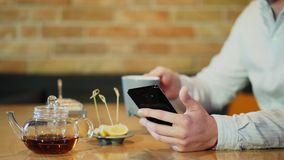 Ο νεαρός άνδρας χρησιμοποιεί το smartphone ενώ έχοντας το πρόγευμα σε έναν καφέ φιλμ μικρού μήκους