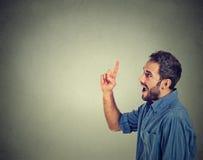 Ο νεαρός άνδρας έχει μια ιδέα, που δείχνει με το δάχτυλο ανατρέχοντας επάνω Στοκ Φωτογραφίες