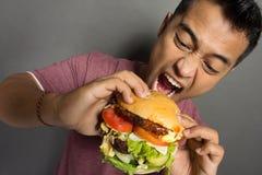 Ο νεαρός άνδρας έχει μια μεγάλη επιθυμία να φάει burger στοκ εικόνες