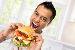 Ο νεαρός άνδρας έχει μια μεγάλη επιθυμία να φάει burger στοκ φωτογραφία
