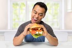 Ο νεαρός άνδρας έχει μια μεγάλη επιθυμία να φάει burger στοκ φωτογραφία με δικαίωμα ελεύθερης χρήσης