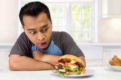 Ο νεαρός άνδρας έχει μια μεγάλη επιθυμία να φάει burger στοκ εικόνες με δικαίωμα ελεύθερης χρήσης