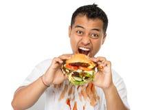 Ο νεαρός άνδρας έχει μια μεγάλη επιθυμία να φάει burger στοκ φωτογραφίες με δικαίωμα ελεύθερης χρήσης