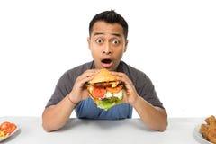 Ο νεαρός άνδρας έχει μια μεγάλη επιθυμία να φάει burger στοκ εικόνα με δικαίωμα ελεύθερης χρήσης