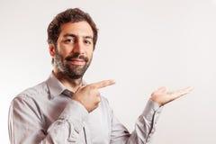 Ο νεαρός άνδρας δίνει τους αντίχειρες επάνω και κάνει τη χειρονομία με Στοκ Φωτογραφίες