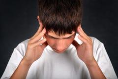 Ο νεαρός άνδρας αισθάνεται τον πονοκέφαλο στοκ εικόνες