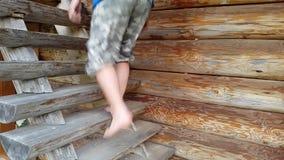 Ο νεαρός άνδρας αναρριχείται επάνω σε μια ξύλινη σκάλα απόθεμα βίντεο