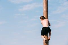 Ο νεαρός άνδρας αναρριχείται σε μια ξύλινη θέση στις παραδοσιακές διακοπές ded Στοκ Εικόνες