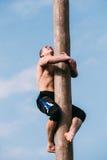 Ο νεαρός άνδρας αναρριχείται σε μια ξύλινη θέση στις παραδοσιακές διακοπές ded Στοκ Φωτογραφίες
