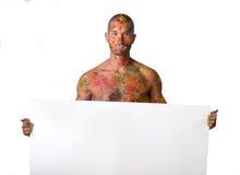 Ο νεαρός άνδρας γυμνοστήθων με το δέρμα χρωμάτισε παντού να κρατήσει το κενό άσπρο σημάδι Στοκ φωτογραφία με δικαίωμα ελεύθερης χρήσης
