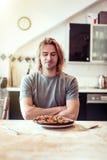 Ο νεαρός άνδρας είναι δυστυχισμένος με τη μμένη πίτσα του για το μεσημεριανό γεύμα Στοκ εικόνα με δικαίωμα ελεύθερης χρήσης
