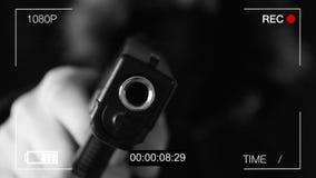 Ο νεαρός άνδρας δείχνει το πυροβόλο όπλο στην κρυμμένη κάμερα, μαύρο υπόβαθρο απόθεμα βίντεο