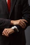 Ο νεαρός άνδρας εξετάζει το ρολόι του Στοκ φωτογραφία με δικαίωμα ελεύθερης χρήσης