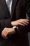 Ο νεαρός άνδρας εξετάζει το ρολόι του Στοκ Φωτογραφίες