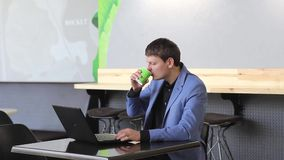 Ο νεαρός άνδρας εργάζεται στο lap-top του για να πάρει όλη την επιχείρησή του γίνοντη νωρίς στον καφέ με το φλιτζάνι του καφέ του απόθεμα βίντεο