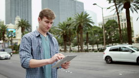 Ο νεαρός άνδρας ελέγχει έναν χάρτη με τη χρησιμοποίηση του PC ταμπλετών του απόθεμα βίντεο