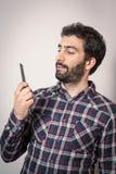 Ο νεαρός άνδρας θέλει τη χτένα η γενειάδα του και moustaches Στοκ φωτογραφία με δικαίωμα ελεύθερης χρήσης